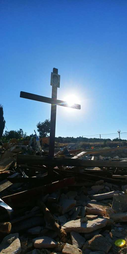 Cross left by family in the rubble
